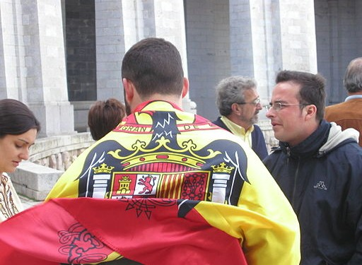 Visitors of the controversial monument at The Valle de los Caídos (Valley of the Fallen) near Madrid sporting a flag of Spain under Franco © RomanD | Wikimedia Commons.