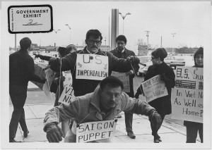 "Protesters carry signs and act out ""Saigon Puppet"" demonstration in front of Wichita City Building, 1967 © Unknown 