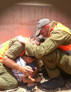 IDF officers shield a 4-year-old boy, protecting him with their own bodies during a Hamas rocket attack, July 15, 2014 © Li Aviv Dadon | Flickr