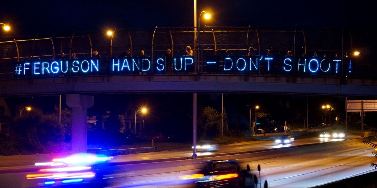 "A police squadron passes underneath a Michael Brown ""Hands Up Don't Shoot"" display © Overpass Light Brigade 