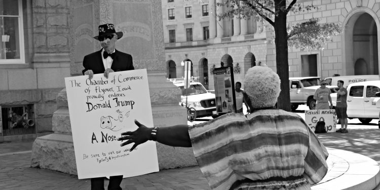 A Trump supporter engages a Trump critic with a sign © Shamila Chaudhary | Flickr
