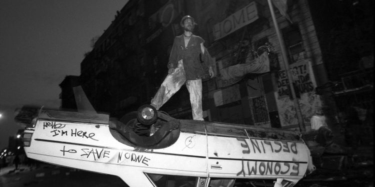 Squatters attempt to defend their building by blocking the street with overturned cars and trash before an expected attack by the police on East 13th Street. © Andrew Lichtenstein