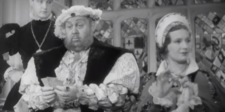 Plump clueless Charles Laughton as Henry sitting between his wife Lady Katherine Howard (Binnie Barnes) and her lover (Robert Donat) before executing both. © London Film Productions (public domain)